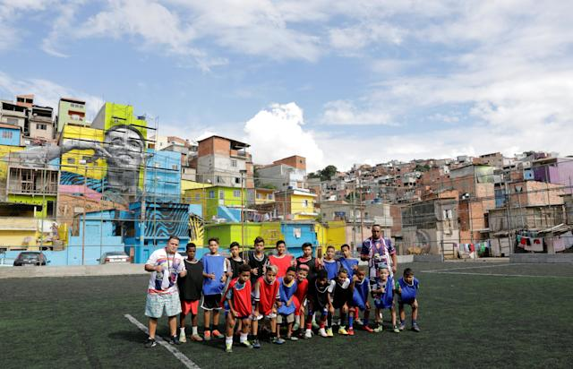 An amateur soccer team pose for a photograph with the image of Brazil' soccer player Gabriel Jesus painted on the walls of houses in the neighbourhood he lived in during his childhood in Sao Paulo, Brazil May16, 2018. REUTERS/Paulo Whitaker