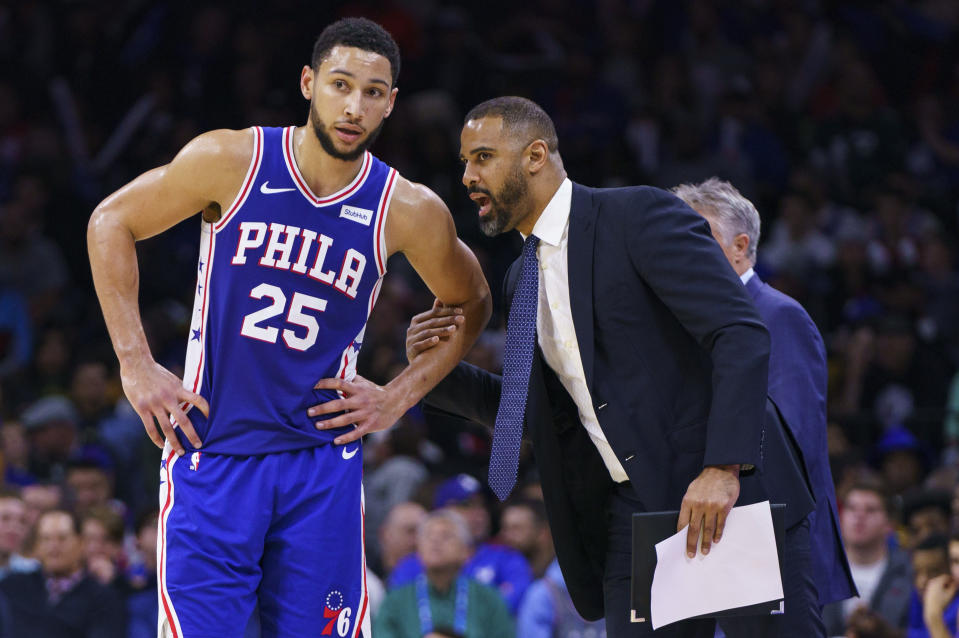 FILE - Philadelphia 76ers' Ben Simmons, left, listens to assistant coach Ime Udoka, right, during the second half of an NBA basketball game against the Sacramento Kings in Philadelphia, in this Wednesday, Nov. 27, 2019, file photo. New Celtics coach Ime Udoka says it became evident early this offseason that of the open NBA jobs, Boston was the best available because of the talent on its roster. (AP Photo/Chris Szagola, File)