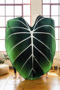 This photo provided by Green Philosophy Co. shows their blanket in the shape of a tropical leaf. They've partnered with nonprofit Trees for the Future, so pillow and throw sales support planting initiatives worldwide. (Sarah Eichstedt/Green Philosophy Co. via AP)