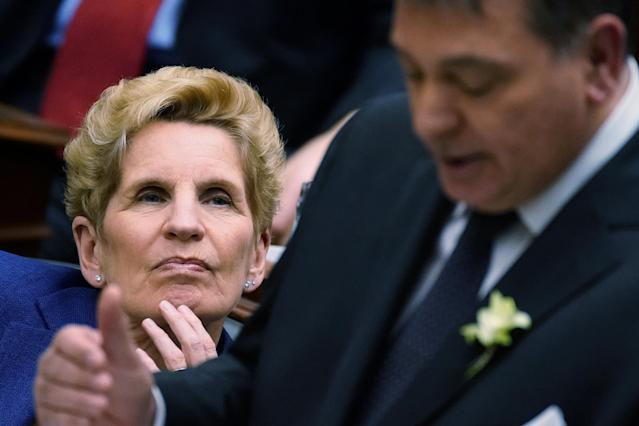 Ontario Premier Kathleen Wynne listens as Finance Minister Charles Sousa reads the new provincial budget at Queen's Park in Toronto, Ontario, Canada, March 28, 2018. REUTERS/Carlo Allegri