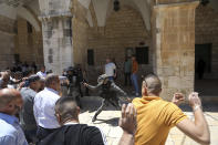 Israeli border police swing their batons at Muslim worshippers to prevent them from gathering for Friday prayers at the Dome of the Rock Mosque in the Al-Aqsa Mosque compound in the Old City of Jerusalem, Friday, May 14, 2021. (AP Photo/Mahmoud Illean)