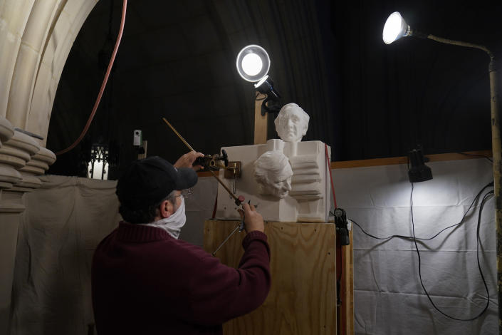 Stone carver Sean Callahan works with a pointing machine on plaster models from a sculpture by Chas Fagan of Holocaust survivor and Nobel Peace Prize winning author Elie Wiesel in the Human Rights Porch at the Washington National Cathedral, Friday, March 12, 2021. The tool is used to accurately copy plaster sculpture models into stone. (AP Photo/Carolyn Kaster)