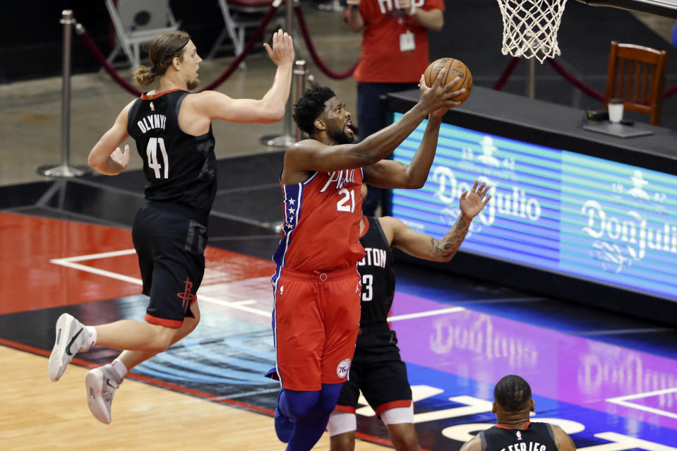 Philadelphia 76ers center Joel Embiid (21) gets a shot up past Houston Rockets forward Kelly Olynyk (41) and guard Kevin Porter Jr., right, during the second half of an NBA basketball game Wednesday, May 5, 2021, in Houston. (AP Photo/Michael Wyke, Pool)