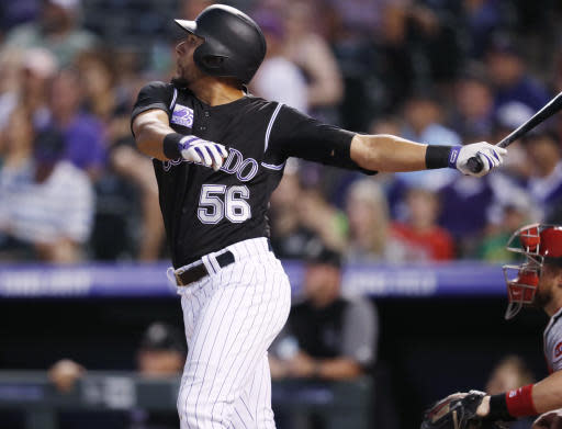 Colorado Rockies pinch-hitter Noel Cuevas follows the flight of his RBI-triple off Cincinnati Reds starting pitcher Sal Romano in the sixth inning of a baseball game Friday, May 25, 2018, in Denver. (AP Photo/David Zalubowski)