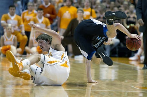 Tennessee's Skylar McBee and UNC Asheville's Matt Dickey get tripped up as they both chased after at loose ball during an NCAA college basketball game at Thompson-Boling Arena on Tuesday, Dec. 20, 2011 in Knoxville, Tenn. (AP Photo/News Sentinel, Saul Young)