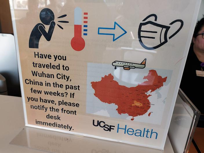 "Warning sign with text reading ""Have you traveled to Wuhan City, China, in the past few weeks? If you have, please notify the front desk immediately"" at the University of California, San Francisco (UCSF) medical center on January 28, 2020."