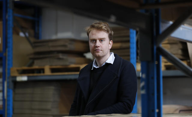 Charlie Pool, the CEO of Stowga, poses for a portrait in the Lovespace warehouse in Dunstable, England, Monday, Jan. 14, 2019. Lovespace, which collects boxes from customers, stores them and then returns the goods when needed, says revenue from businesses doubled over the past year as enterprises large and small began stockpiling inventory because of concerns they will be cut off from suppliers if Britain leaves the European Union without an agreement on future trading relations. (AP Photo/Alastair Grant)