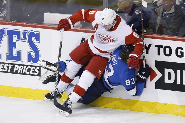 Winnipeg Jets' Sami Niku (83) is checked by Detroit Red Wings' Justin Abdelkader (8) during the first period of an NHL hockey game Friday, Jan. 11, 2019, in Winnipeg, Manitoba. (John Woods/The Canadian Press via AP)