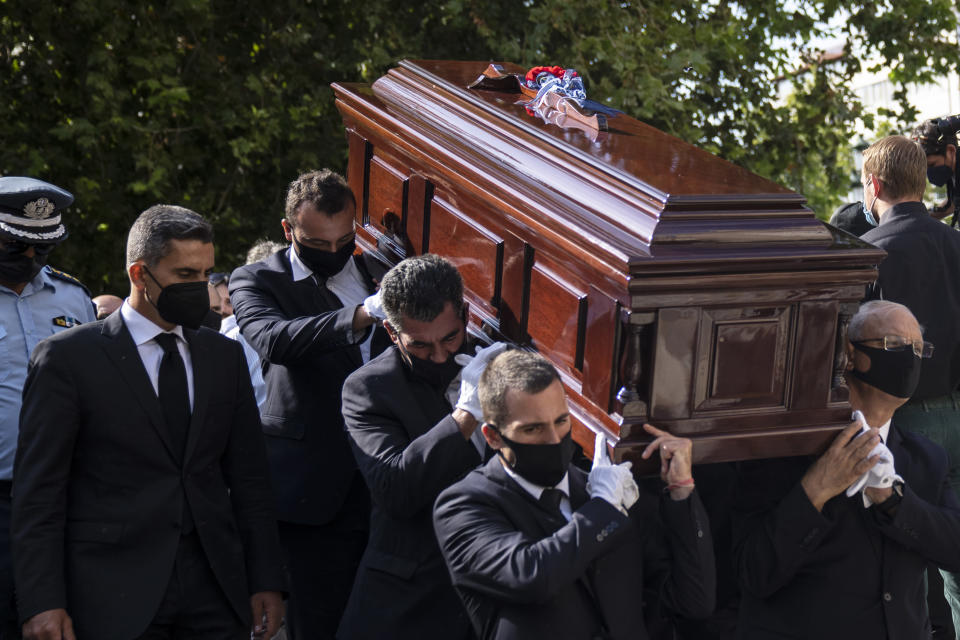Pallbearers carry the coffin of late Greek composer, Mikis Theodorakis in Athens on Monday Sept. 6, 2021. Hundreds of people have gathered outside Athens Cathedral where Greek composer and politician Mikis Theodorakis is to lie in state in a chapel of the cathedral for three days ahead of his burial on the southern island of Crete.(AP Photo/Petros Giannakouris)