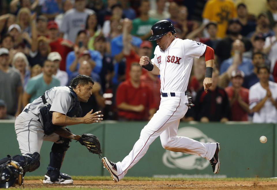 Boston Red Sox's Jacoby Ellsbury, right, scores on a single by Dustin Pedroia as Seattle Mariners' Henry Blanco, left, waits for the throw in the ninth inning of a baseball game in Boston, Thursday, Aug. 1, 2013. The Red Sox won 8-7. (AP Photo/Michael Dwyer)