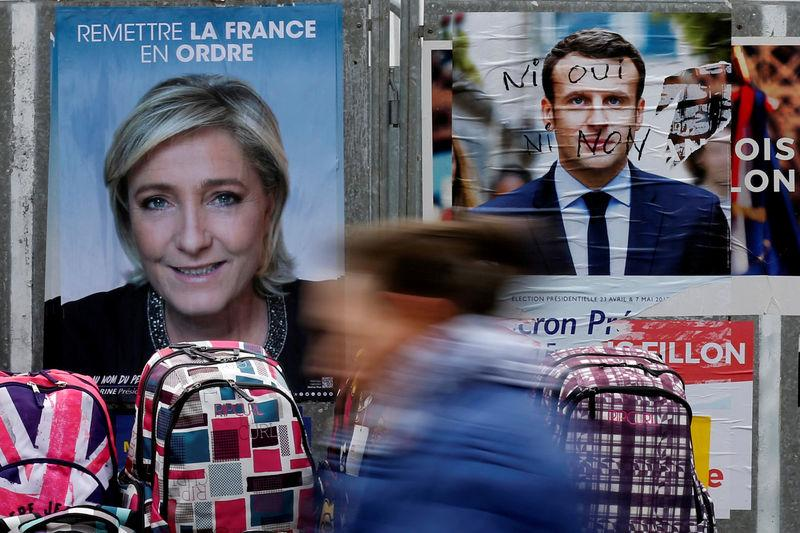 A woman walks past official posters of candidates for the 2017 French presidential election Marine Le Pen and Emmanuel Macron at a local market in Bethune