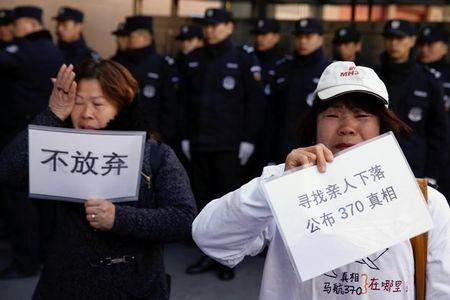 "Relatives of passengers aboard Malaysia Airlines flight MH370, which went missing in 2014, hold up placards outside the foreign ministry in Beijing, China, March 8, 2017. The placards read: ""Don't give up"" and ""We are looking for the whereabouts of our relatives. Release the truth about 370.""   REUTERS/Thomas Peter/Files"
