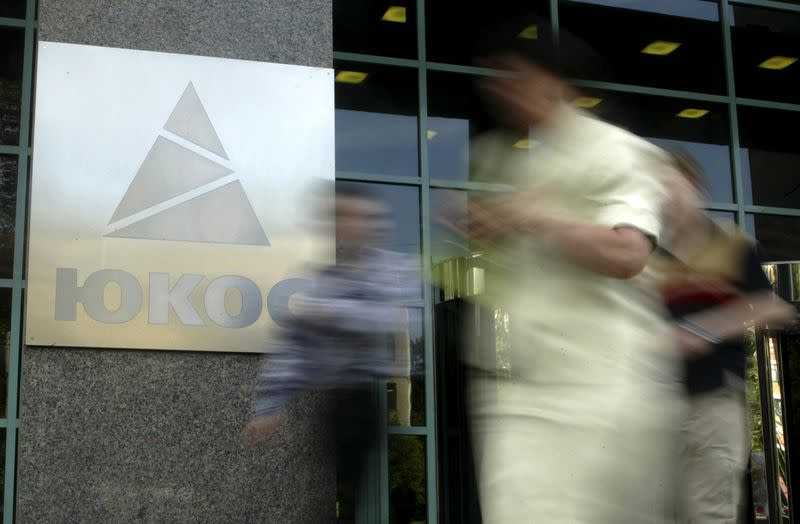File photo of people walking by the Yukos oil company headquarters in Moscow