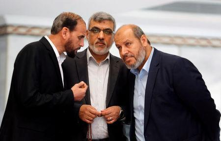 Hamas leaders Izzat Reshiq (C) and Khalil al-Hayya (R) chat during a reconciliation deal signing ceremony in Cairo, Egypt, October 12, 2017. REUTERS/Amr Abdallah Dalsh