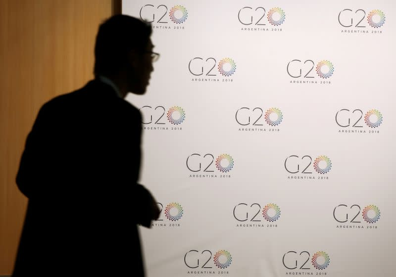 FILE PHOTO: A man stands next to a board with the G20 Meeting of Finance Ministers logo in Buenos Aires