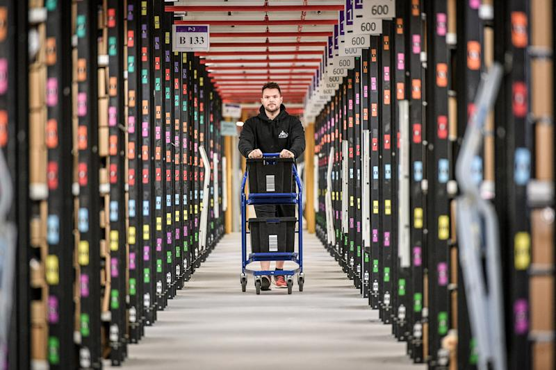 A worker walks between thousands of racks at Amazon's fulfillment centre in Swansea. Photo: Ben Birchall/PA Archive/PA Images