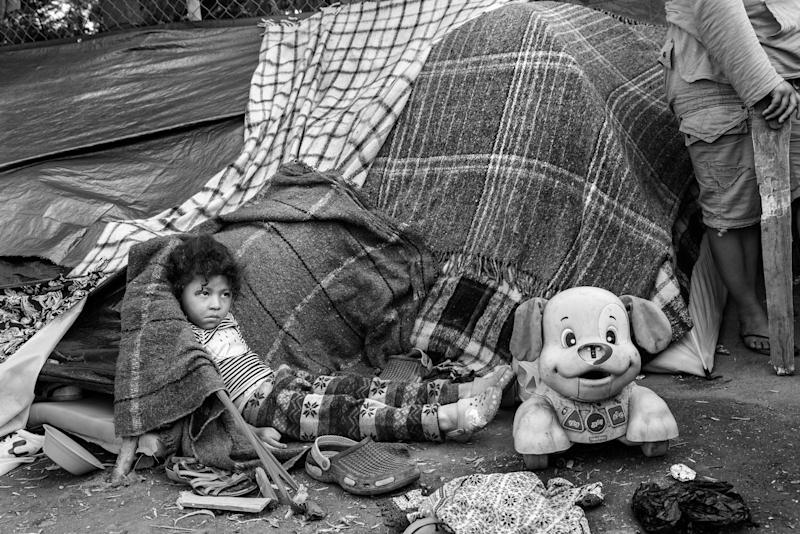 Ana rests against her tent inside Benito Juraez, a massive shelter in Tijuana, Mexico. Ana and her parents traveled from Honduras hoping to cross into the United States, but amidst the chaos at the border, they sought refuge at the shelter.
