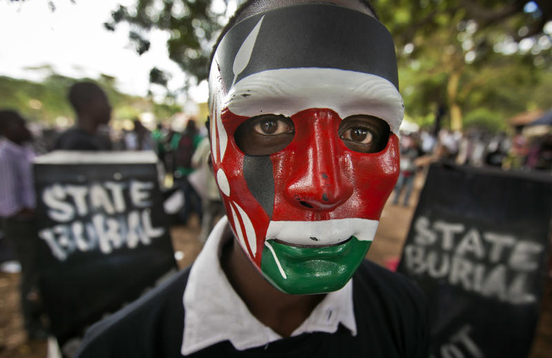"A demonstrator wears a mask in the colors of the Kenyan flag as he stands next to mock coffins, on which are written ""State Burial, Ballot Revolution"", before demonstrators carried the coffins to the Parliament and burned them, in Nairobi, Kenya Wednesday, Jan. 16, 2013. Hundreds of demonstrators angered at outgoing Kenyan legislators, whose term ended earlier this week and who earn about $175,000 a year in a country where the average annual income is $1,700, doused 221 mock coffins with gasoline, one for each legislator, to protest against last week's attempt to award themselves a $110,000 bonus, which was vetoed by the president. (AP Photo/Ben Curtis)"