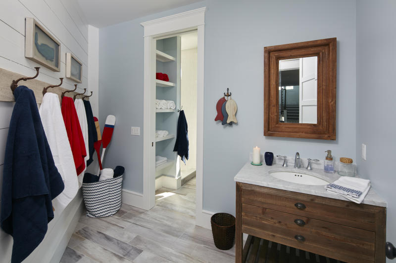 "This photo provided by Marnie Homes shows a bathroom and bedroom area designed by Marnie Oursler. Kids are more likely to place items on shelves, especially if they can drop clothing in baskets, or use hooks rather than hangers to put away their clothing, says designer and builder Oursler, host of the DIY Networks series ""Big Beach Builds."" (Dana Hoff/Marnie Homes via AP)"