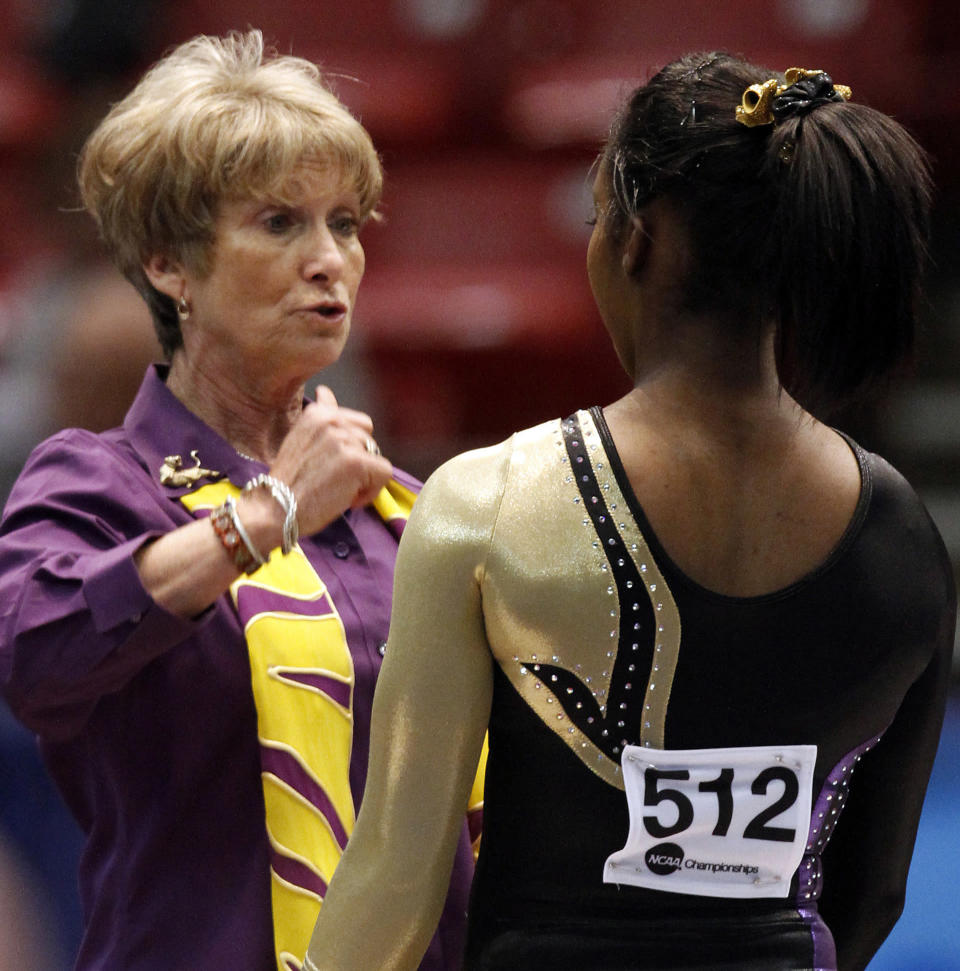 FILE- In this April 18, 2014, file photo, LSU coach D-D Breaux talks with Britney Ranzy before her routine on the floor exercise at the NCAA women's gymnastics championships in Birmingham, Ala. Breaux has announced she will will retire after a 43-season career during which the Tigers finished in the top 10 nationally 31 times. (AP Photo/Butch Dill, File)