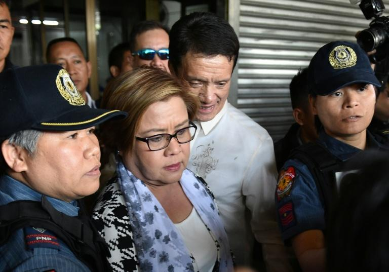 Philippine Senator Leila De Lima (C), a top critic of President Rodrigo Duterte, is escorted by police officers and her lawyer Alex Padilla (R) after her arrest at the Senate in Manila on February 24, 2017