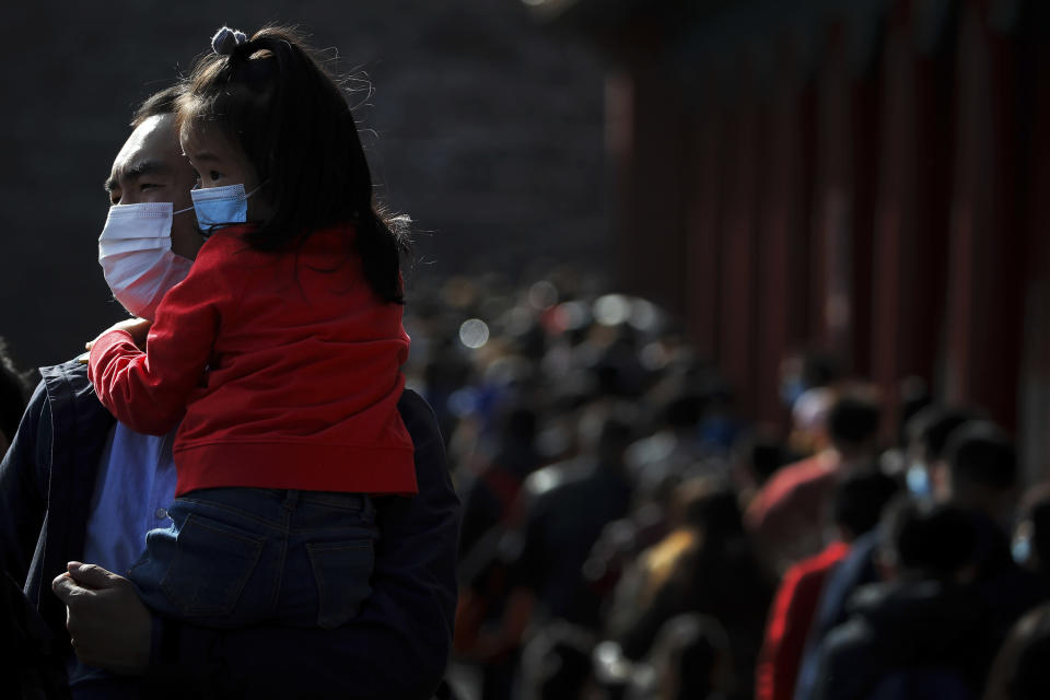 A man holds a child, both wearing face masks to help curb the spread of the coronavirus line up with visitors to enter an exhibition held at the Forbidden City in Beijing, Saturday, Nov. 7, 2020. China on Saturday reported 33 new confirmed coronavirus infections, all of which the National Health Commission said were in patients who contracted the virus abroad. (AP Photo/Andy Wong)
