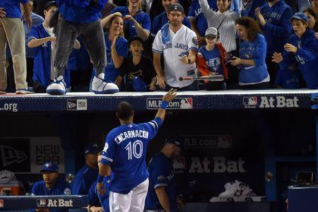 Toronto Blue Jays first baseman Edwin Encarnacion (10) gives a bat to a fan after the Cleveland Indians beat the Toronto Blue Jays in game five of the 2016 ALCS playoff baseball series at Rogers Centre. Mandatory Credit: Dan Hamilton-USA TODAY Sports