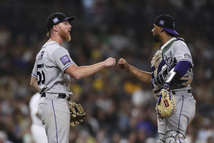 Colorado Rockies starting pitcher Jon Gray, left, bumps fists with catcher Elias Diaz as he is removed from the baseball game against the San Diego Padres in the seventh inning Friday, July 30, 2021, in San Diego. (AP Photo/Derrick Tuskan)