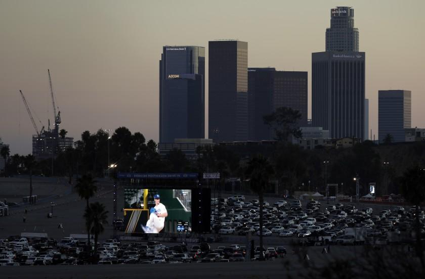 LOS ANGELES, CA - OCTOBER 12: Fans drive into Dodger Stadium on Monday, Oct. 12, 2020 in Los Angeles, CA for a drive-in viewing party for the National League Championship Series against the Atlanta Braves in Arlington, Texas. (Myung J. Chun / Los Angeles Times)