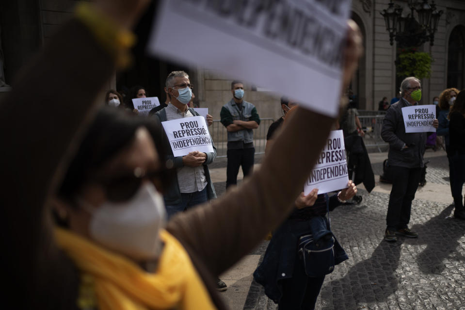 """Demonstrators holding placards reading in Catalan """"stop repression, Independence"""" take part in a protest to condemn a police raid on Catalan separatists in Barcelona, Spain, Wednesday, Oct. 28, 2020. Spanish officials say that police have arrested 21 individuals with links to the Catalan separatist movement on suspicion of corruption and promoting public disorder. (AP Photo/Emilio Morenatti)"""