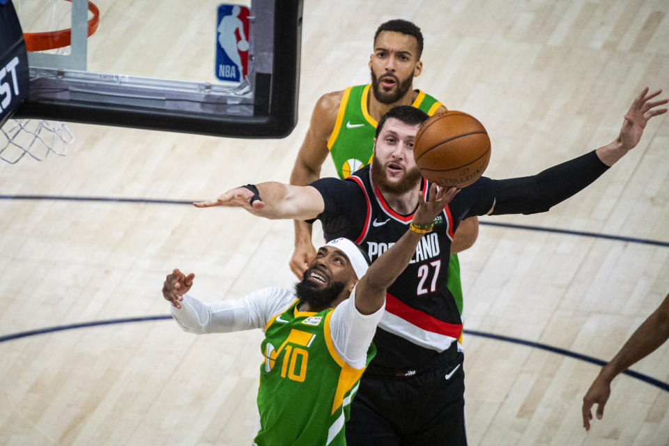 Utah Jazz guard Mike Conley (10) lays the ball up while guarded by Portland Trail Blazers center Jusuf Nurkic (27) during the first half of an NBA basketball game Thursday, April 8, 2021, in Salt Lake City. (AP Photo/Isaac Hale)