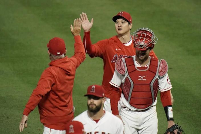 The Angels' Shohei Ohtani, top, gives manager Joe Maddon a high-five while celebrating a 9-2 win against the Dodgers.