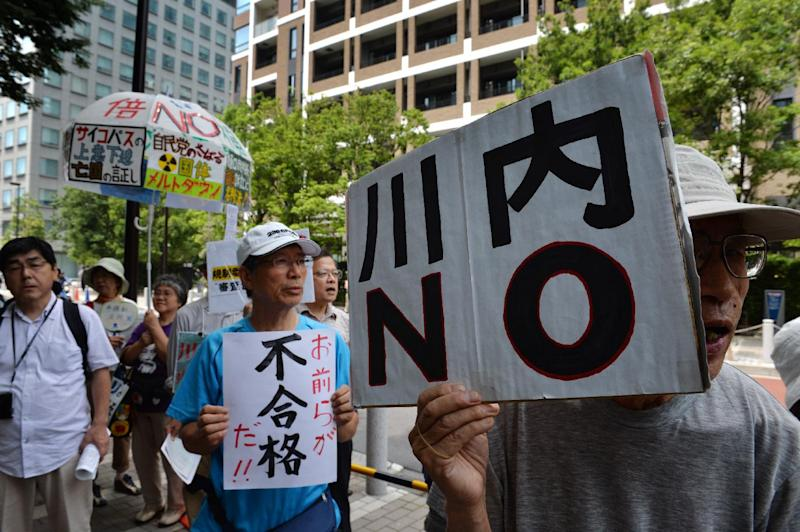 """An anti-nuclear protester holds a placard reading """"Sendai NO"""" during a rally in Tokyo on July 16, 2014 (AFP Photo/Kazuhiro Nogi )"""