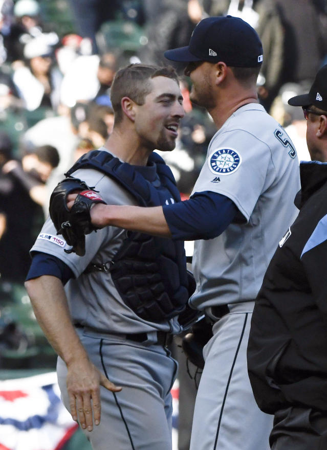 Seattle Mariners catcher Tom Murphy, left,and relief pitcher Connor Sadzeck embrace after a baseball game against the Chicago White Sox in Chicago, Saturday, April 6, 2019. The Mariners won 9-2. (AP Photo/Matt Marton)