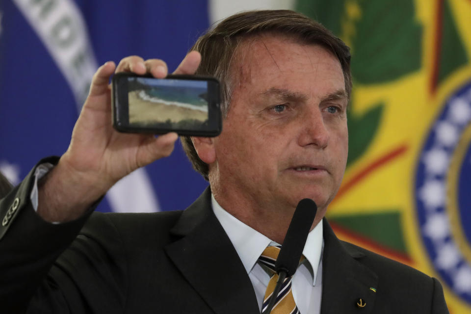 Brazil's President Jair Bolsonaro shows a photo of a beach during a ceremony presenting a program to restart tourism, amid the COVID-19 pandemic, at Planalto Palace in Brasilia, Brazil, Tuesday, Nov. 11, 2020. (AP Photo/Eraldo Peres)w