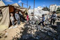 Children gather around a tent that Nazmy al-Dahdouh, a 70-year-old Palestinian man, has set up on top of the ruins of his home, destroyed in recent Israeli air strikes in Gaza City