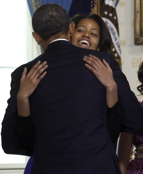 President Barack Obama is hugged by this daughter Malia after being officially sworn-in in the Blue Room of the White House during the 57th Presidential Inauguration in Washington, Sunday Jan, 20, 2013. (AP Photo/Pool, Charles Dharapak)