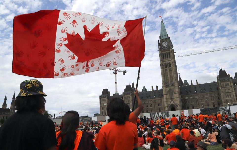 """<span class=""""caption"""">Protesters wave a flag at Parliament Hill in Ottawa at a """"Cancel Canada Day"""" protest in response to the discovery of hundreds of unmarked graves at Indian Residential Schools. THE CANADIAN PRESS/ Patrick Doyle </span> <span class=""""attribution""""><span class=""""source"""">THE CANADIAN PRESS/ Patrick Doyle </span></span>"""
