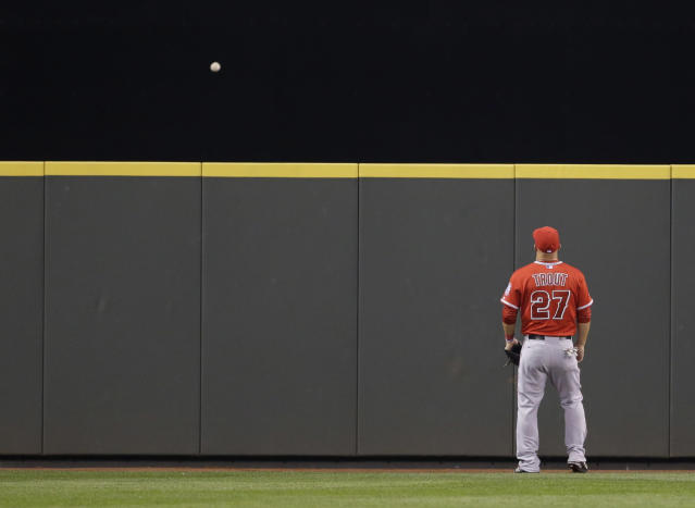 Los Angeles Angels center fielder Mike Trout can only watch as a solo home run hit by Seattle Mariners' Corey Hart goes over the wall in the seventh inning of a baseball game, Tuesday, April 8, 2014, in Seattle. It was Hart's second home run of the game. (AP Photo/Ted S. Warren)