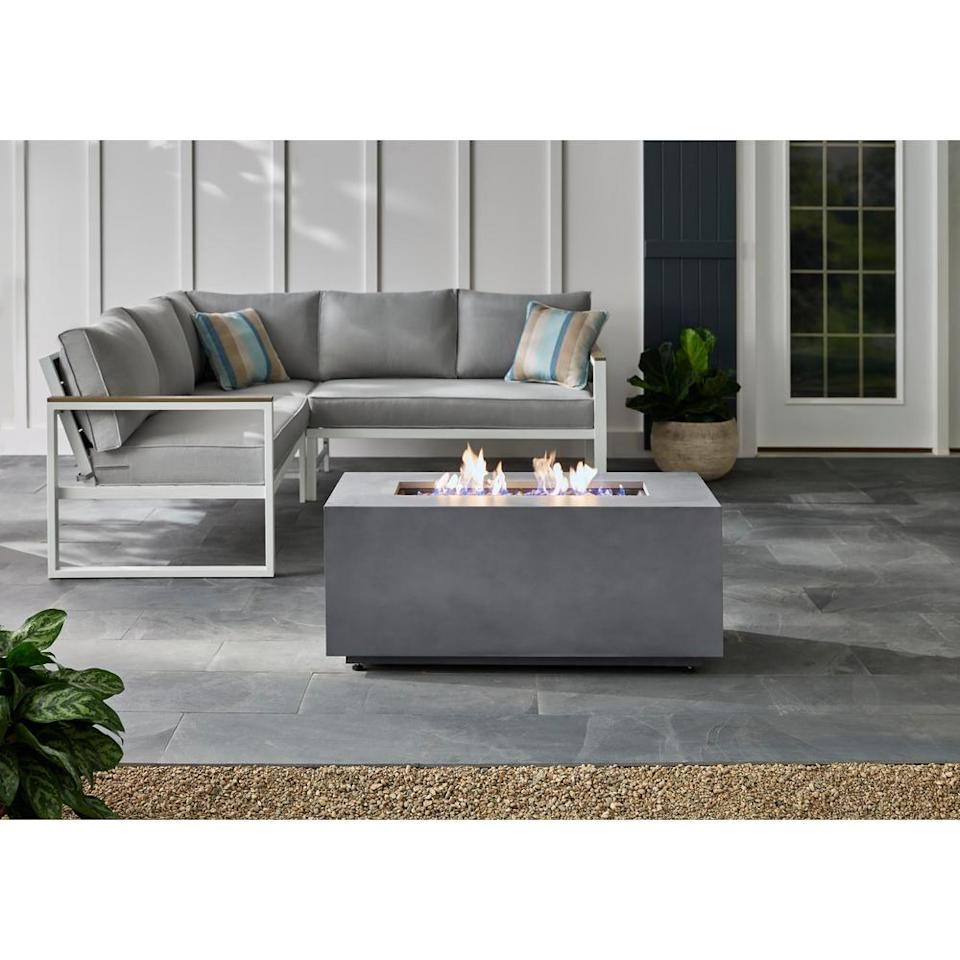 """<p><strong>Hampton Bay</strong></p><p>homedepot.com</p><p><strong>$329.00</strong></p><p><a href=""""https://go.redirectingat.com?id=74968X1596630&url=https%3A%2F%2Fwww.homedepot.com%2Fp%2FHampton-Bay-42-in-x-20-in-Rectangular-Steel-Fire-Pit-Concrete-with-Decorative-Concrete-GFHD42%2F308833376&sref=https%3A%2F%2Fwww.countryliving.com%2Fdiy-crafts%2Fg31966151%2Foutdoor-fireplace-ideas%2F"""" rel=""""nofollow noopener"""" target=""""_blank"""" data-ylk=""""slk:Shop Now"""" class=""""link rapid-noclick-resp"""">Shop Now</a></p><p>If you prefer a sleek, modern look and no mess, you'll love this gas-powered fire table with an adjustable flame.</p>"""