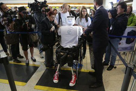 Alexander Herzog (L) and Jeannette Bohg, doctoral student and senior research scientist at Max Planck Society respectively, push 'Athena', the first 'humanoid' robot to fly as a passenger, as  they arrive at Los Angeles International Airport, California December 15, 2014. REUTERS/Jonathan Alcorn