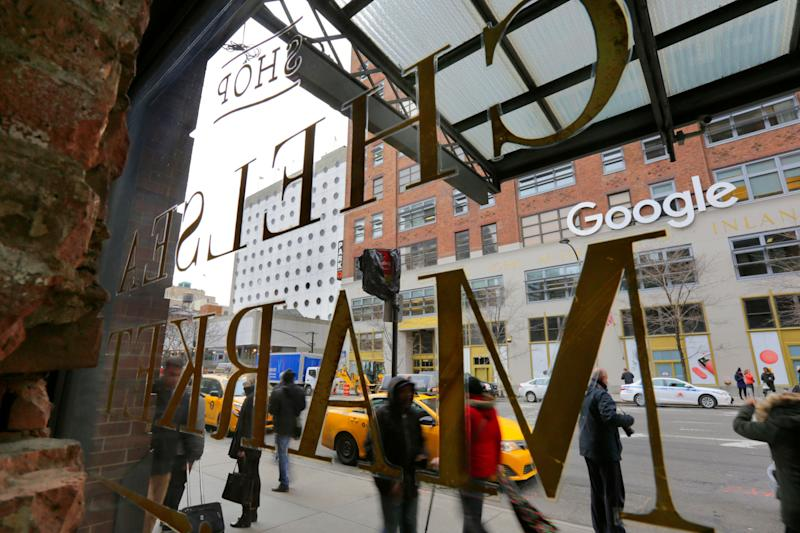 The Chelsea Market building's window sign and the sign for Google's New York City headquarters, are shown in this photo, Tuesday, March 20, 2018. Google Inc. has finalized the $2.4 billion purchase of New York City's Chelsea Market building, the former Nabisco factory, on Tuesday. (AP Photo/Richard Drew)