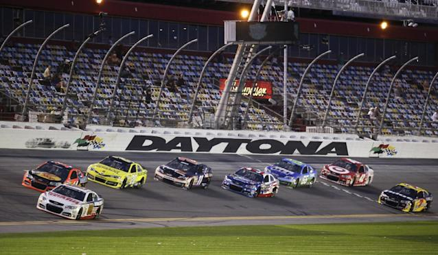 Dale Earnhardt Jr., bottom front, and Tony Stewart, top front, lead a group of cars down the front stretch during an evening practice for the Daytona 500 NASCAR Sprint Cup Series auto race at Daytona International Speedway in Daytona Beach, Fla., Wednesday, Feb. 19, 2014. (AP Photo/John Raoux)