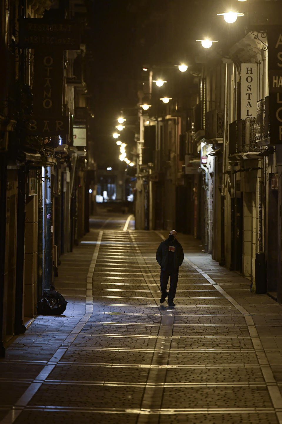 A resident wearing face mask protection walks along an empty San Nicolas street, in Pamplona, northern Spain, Saturday, Oct. 24, 2020, as new measures against the coronavirus began in the Navarra province where all bar and restaurants are closed for 15 days from midnight Wednesday. (AP Photo/Alvaro Barrientos)