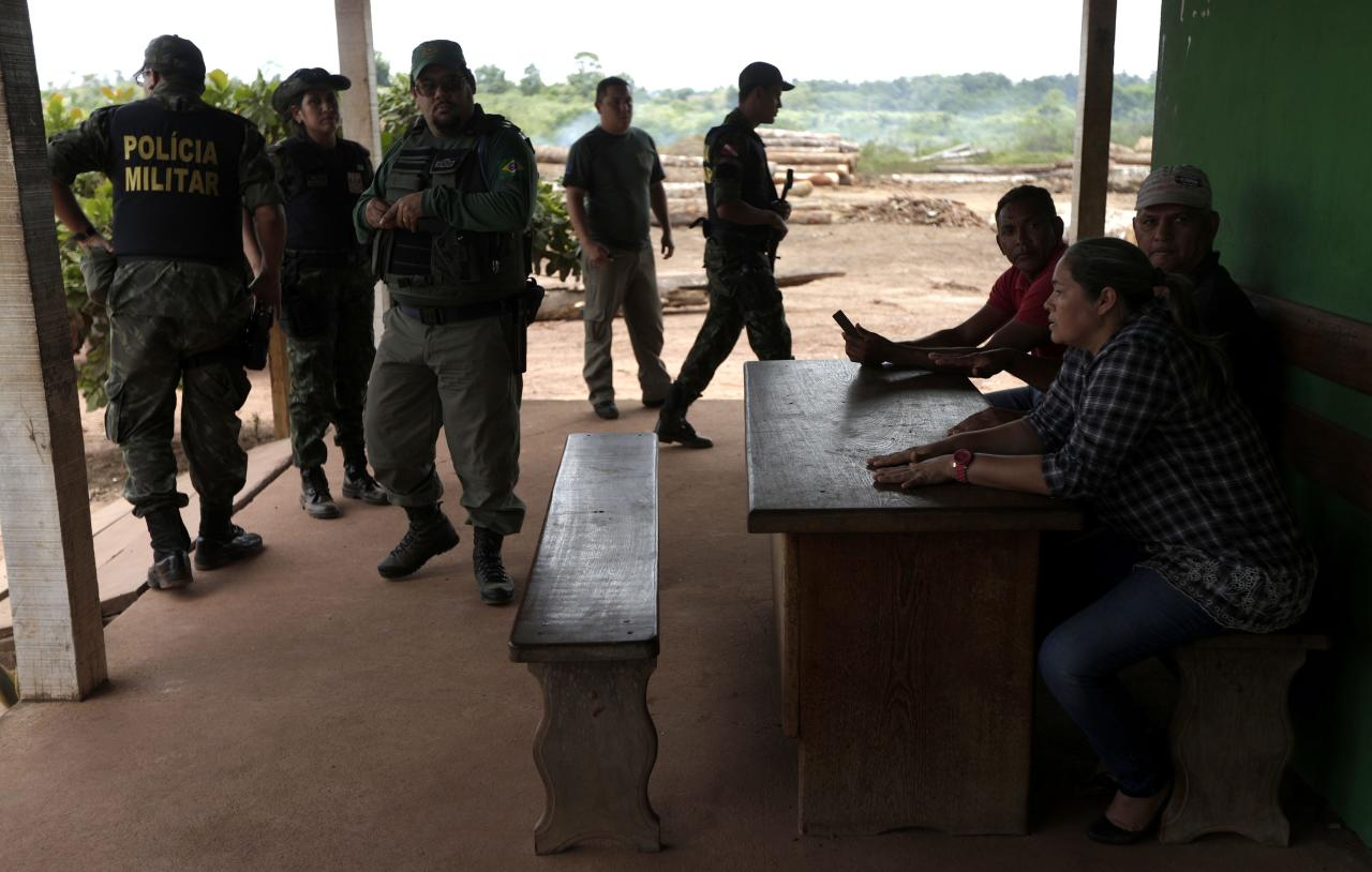 Agent Alex Lacerda (3rd L) of Brazil's Institute for the Environment and Renewable Natural Resources, or IBAMA, and a group of environmental police officers talk with the owners (R) of an illegal sawmill during a sting operation against sawmills, log haulers and loggers who trade in illegally extracted wood from the Alto Guama River indigenous reserve in Nova Esperanca do Piriau, Para state, September 25, 2013. Picture taken September 25, 2013. To match Special Report BRAZIL-DEFOREST/ REUTERS/Ricardo Moraes (BRAZIL - Tags: ENVIRONMENT CRIME LAW POLITICS)