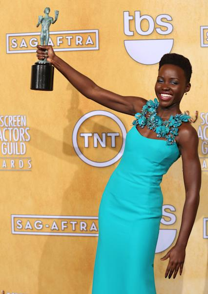 "Lupita Nyong'o poses with the award for outstanding performance by a female actor in a supporting role for ""12 Years a Slave"" in the press room at the 20th annual Screen Actors Guild Awards at the Shrine Auditorium on Saturday, Jan. 18, 2014, in Los Angeles. (Photo by Matt Sayles/Invision/AP)"