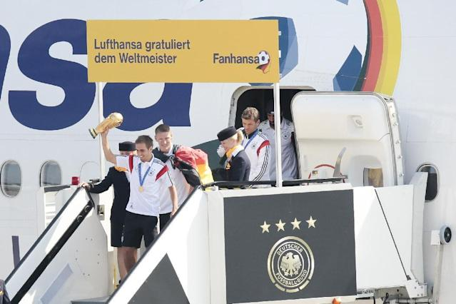 """The players of German national soccer team, Philipp Lahm with trophy , Sebastian Schweinsteiger, Thomas Mueller and Sami Khedira, from left arrive at Tegel airport in Berlin Tuesday, July 15, 2014. Germany's World Cup-winning team has returned home from Brazil to celebrate the country's fourth title with huge crowds of fans. The team's Boeing 747 touched down at Berlin's Tegel airport midmorning Tuesday after flying a lap of honor over the """"fan mile"""" in front of the landmark Brandenburg Gate. Words read Lufthansa congratulates the World Champion, Fanhansa. (AP Photo/Markus Schreiber)"""