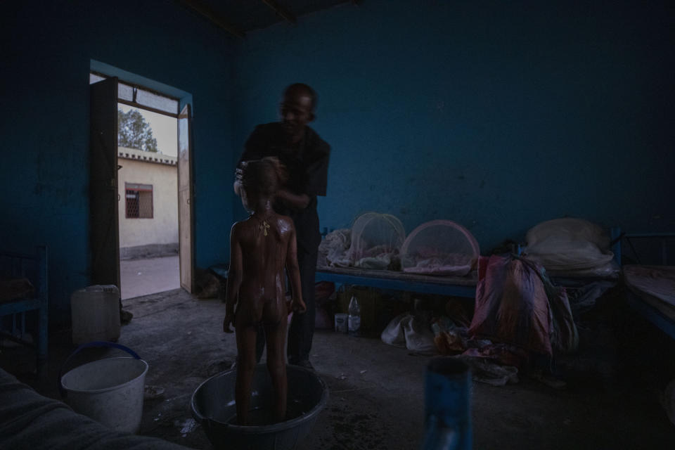 Tigrayan refugee Abraha Kinfe Gebremariam, 40, bathes his 5-year-old son, Micheale, after waking up early in the morning in their shelter in Hamdayet, eastern Sudan, near the border with Ethiopia, on March 21, 2021. (AP Photo/Nariman El-Mofty)