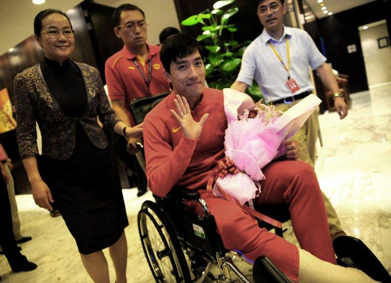 "Chinese hurdler Liu Xiang waves as he arrives back in Shanghai on August 14, 2012, after undergoing the knife in London. Liu's coach said he would make a ""full recovery"" from his ruptured Achilles tendon, but would probably not be in action this year"