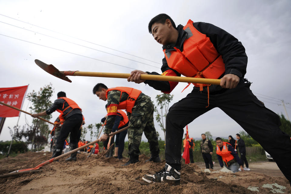 In this photo released by Xinhua News Agency, rescuer workers fortify a temporary dyke against the flooding at the Lianbo Village in Hejin City, in northern China's Shanxi Province, Sunday, Oct. 10, 2021.(Zhan Yan/Xinhua via AP)